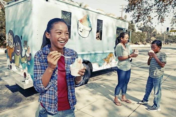 Girl eating ice cream from truck
