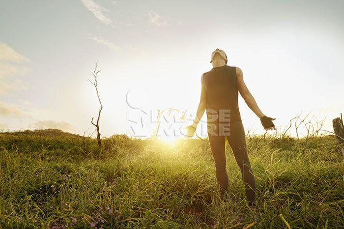 Asian man standing in tall grass