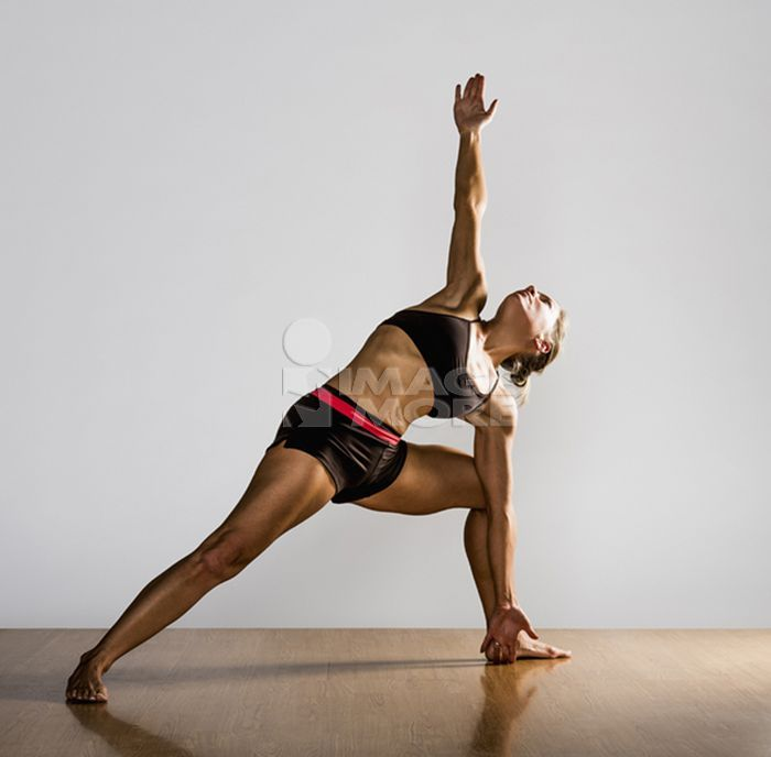 Caucasian woman practicing yoga in studio