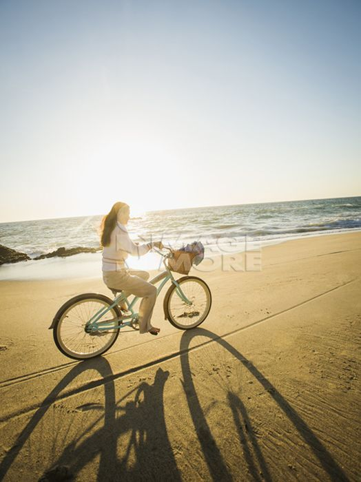 Mixed race woman riding bicycle on beach