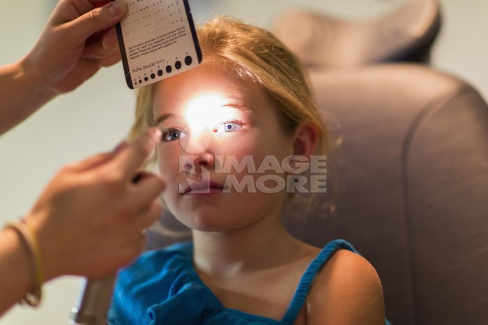 Caucasian girl receiving eye exam