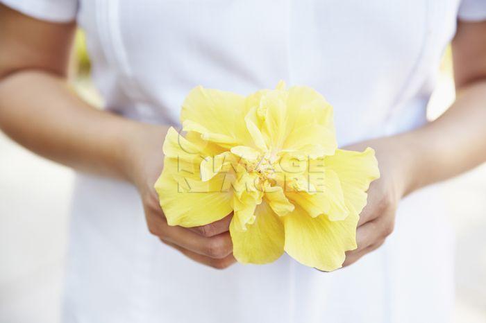Hispanic woman holding tropical flower
