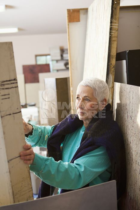 Caucasian artist choosing wood in studio