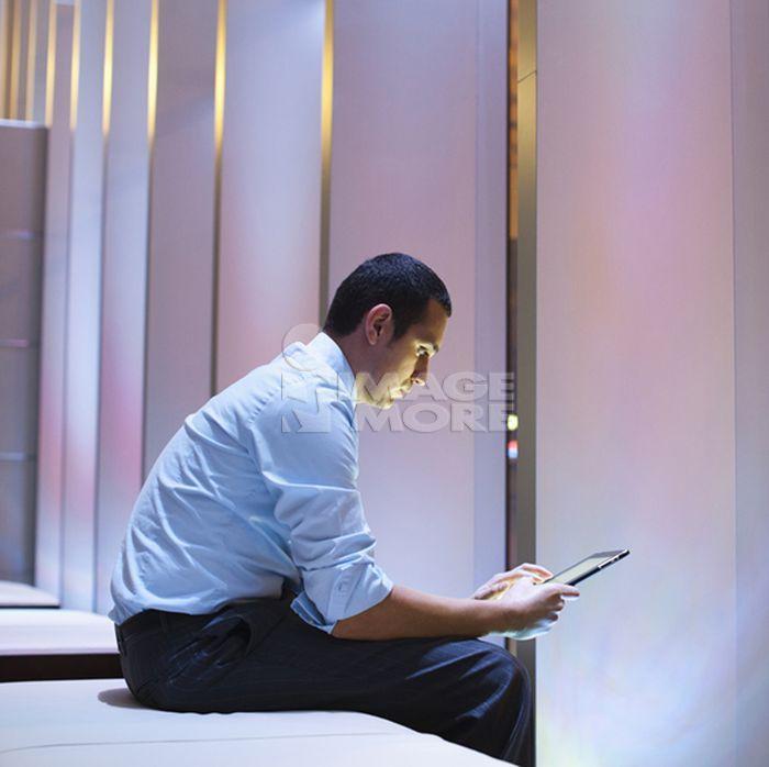 Hispanic businessman sitting on bench using digital tablet