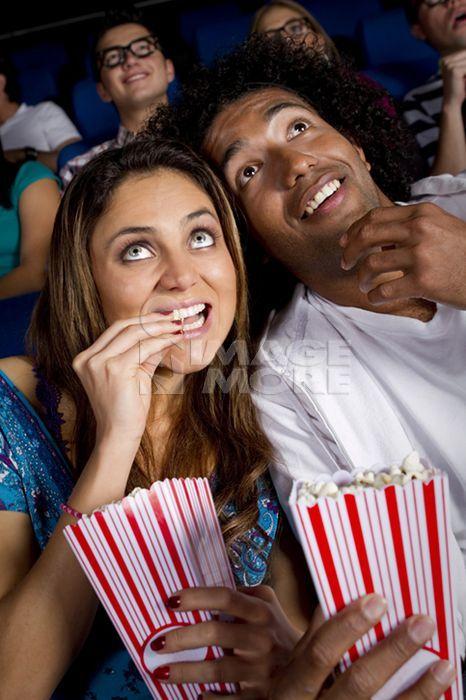 Hispanic couple enjoying popcorn in movie theater