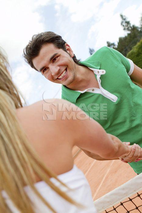 Hispanic couple shaking hands over tennis court net