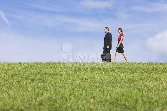 Caucasian co-workers walking through grassy field
