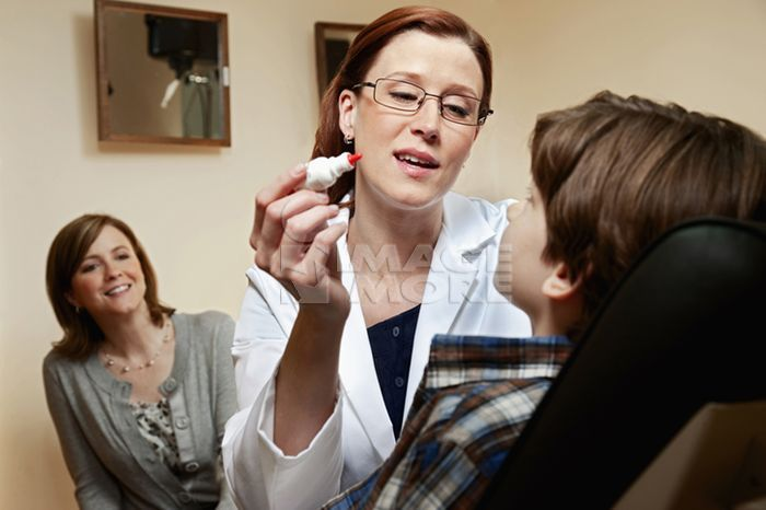 Optician putting drops into patient's eyes