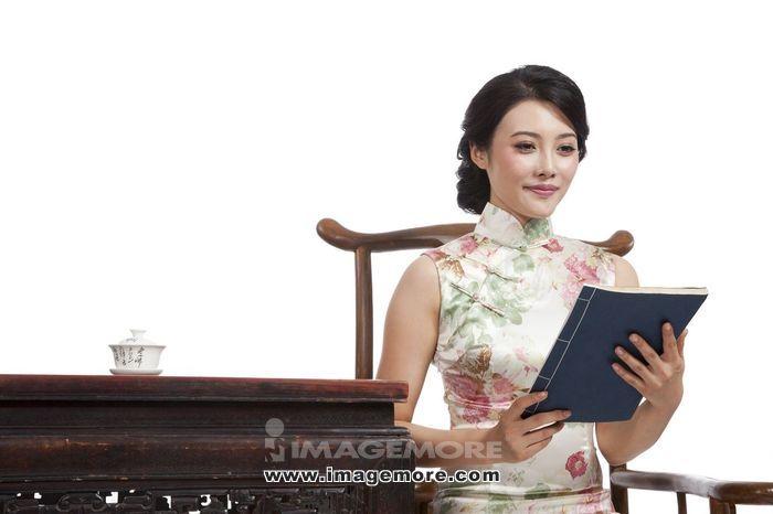 棚拍身穿中国传统服装的年轻女人看书