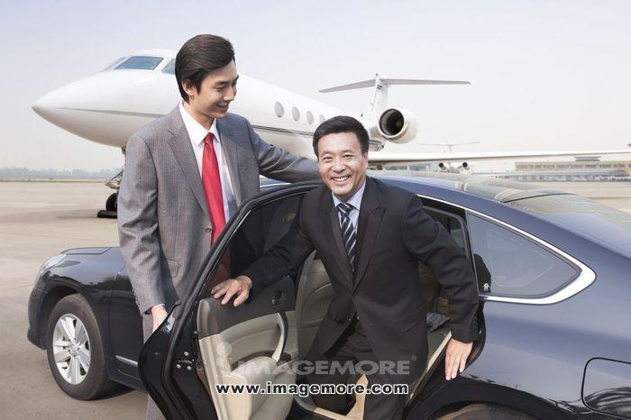 商务男士乘坐轿车抵达机场