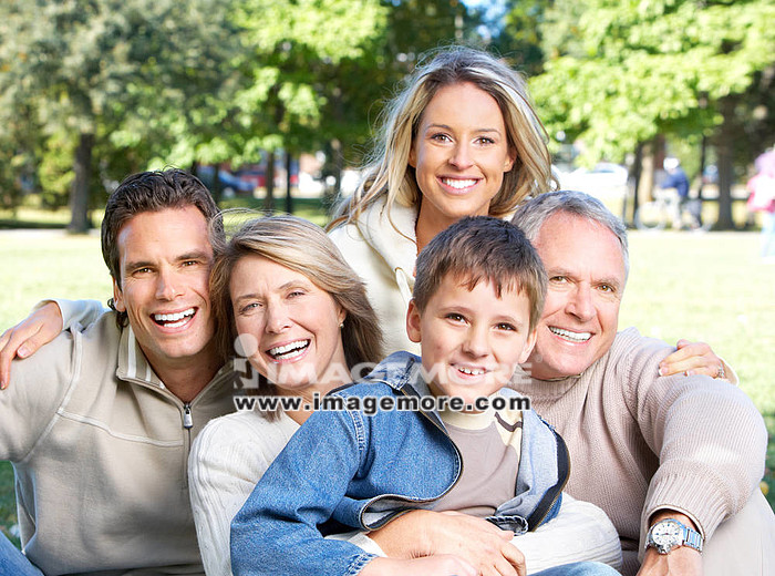 Happy family in park. Grandfather, grandmother, father, mother and son,