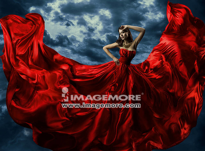 Woman in red evening dress, waving gown with flying long fabric over artistic sky background,