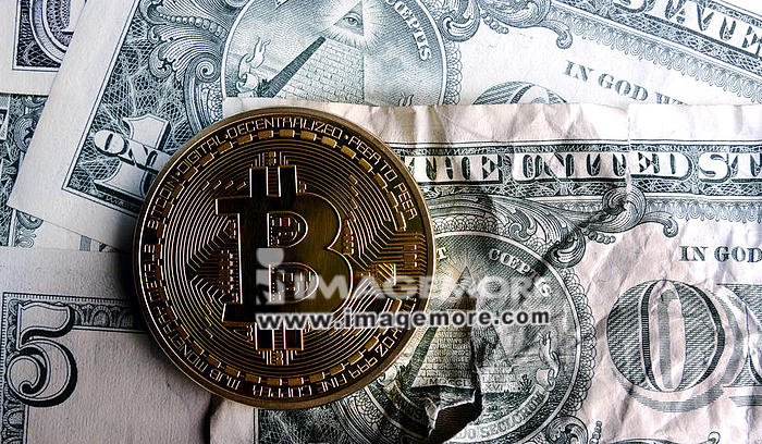 Bitcoin on Crushed  dollar banknote.Concept of  conspiracy,