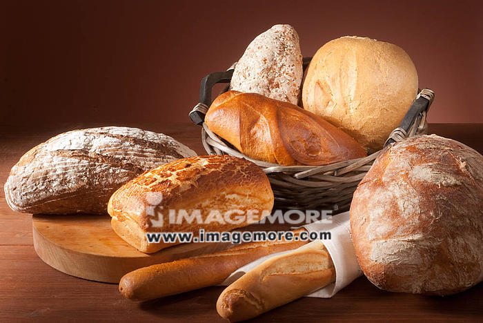 still-life assortment of baked bread over brown background,
