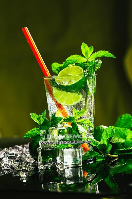 glass of mojito with lime and mint ice cube close-up with red straw.,