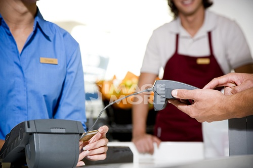 Close up view of a customer paying by credit card in a supermarket