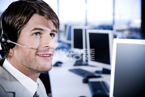 Man with a call centre headset on in a contemporary office
