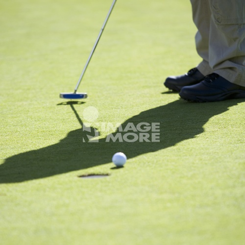 Man playing golf, close-up of feet and putter