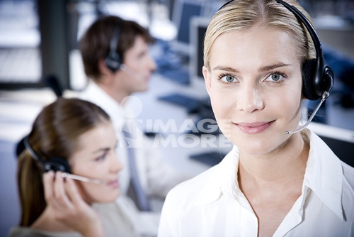 Smiling businesswoman looking at the camera wearing a call centre headset