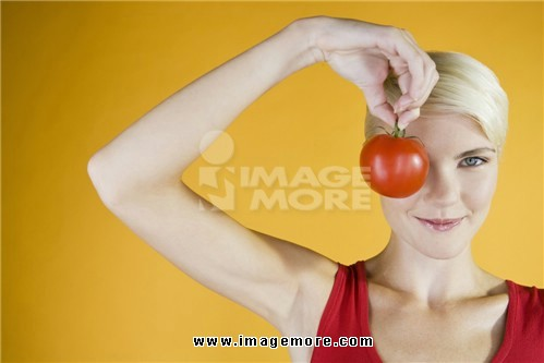 A Young Woman Holding A Tomato In Front Of Her Face