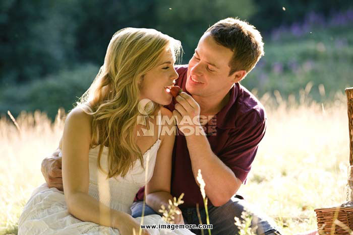 A young man feeding his girlfriend a strawberry, outdoors