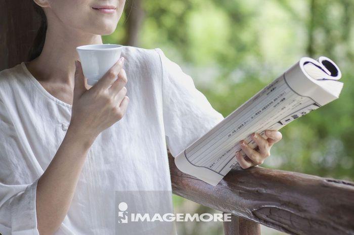 年轻女人拿着古书边喝茶