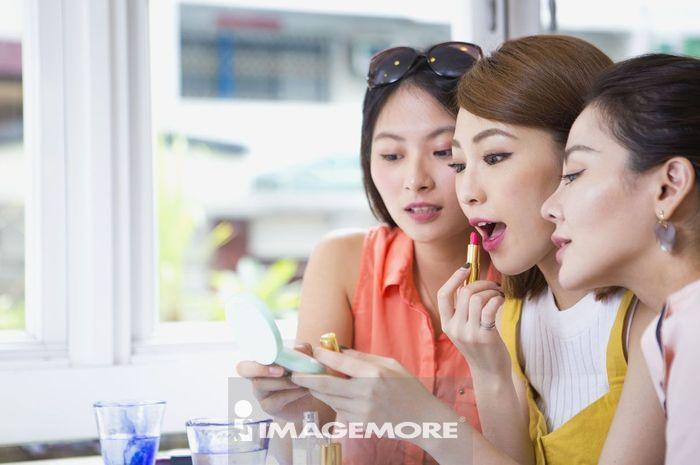 年轻女性在咖啡厅化妆
