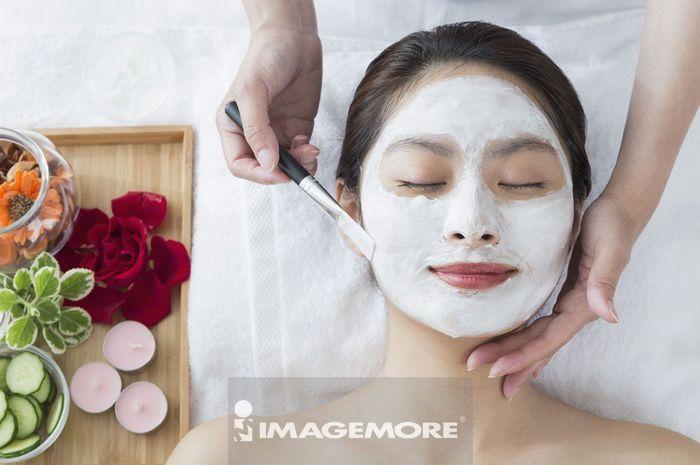 美容师在帮年轻女人敷泥状面膜