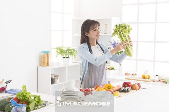 年轻女人拿着一把芹菜