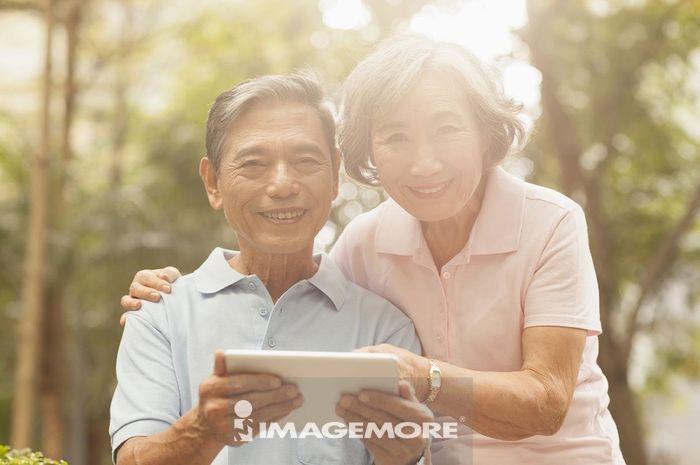 老年夫妻在户外使用平板计算机