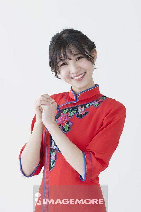 年轻女人穿着旗袍作问候手势