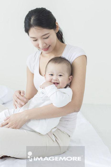 年轻妈妈坐在床上抱着宝宝