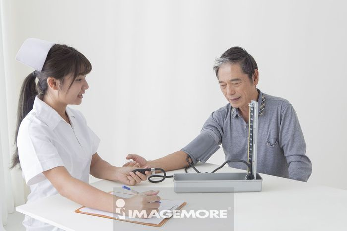 年轻女护士在帮老年男人测量血压