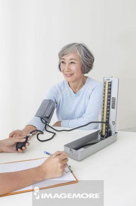 年轻女护士在帮老年女人测量血压