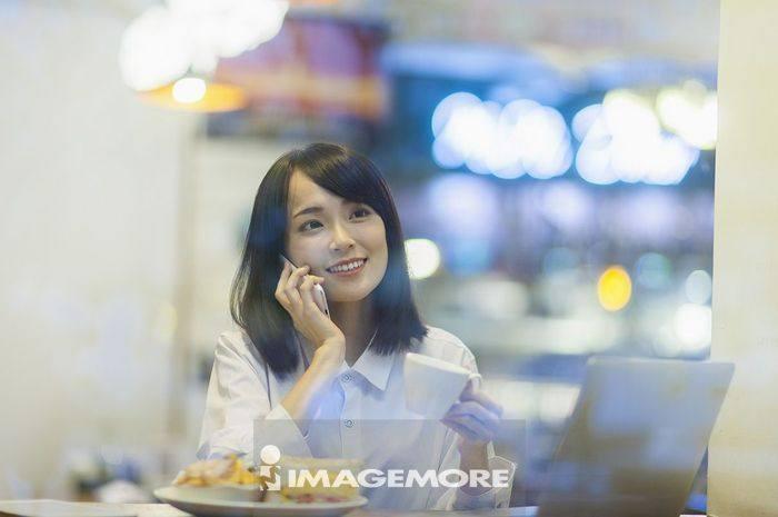 一位办公女性在吃下午茶 讲电话