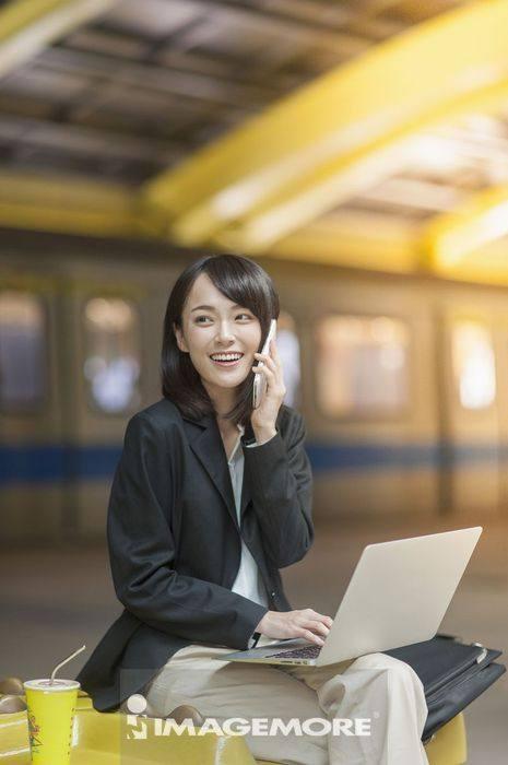 一位办公女性边打电话边使用笔记本电脑