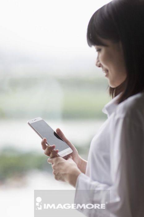 一位办公女性在使用智能型手机
