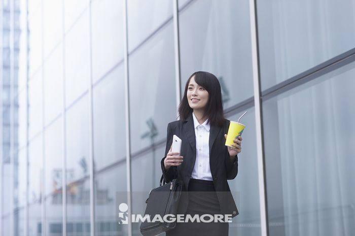 一位办公女性拿着咖啡