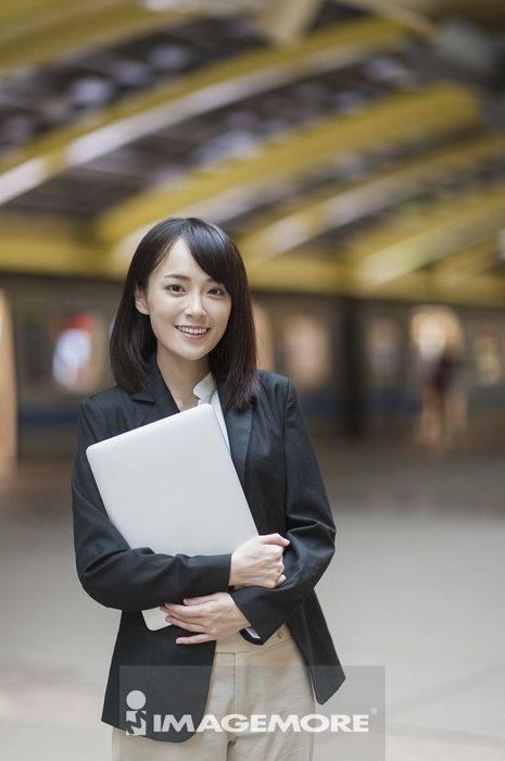 一位办公女性拿着笔记本电脑