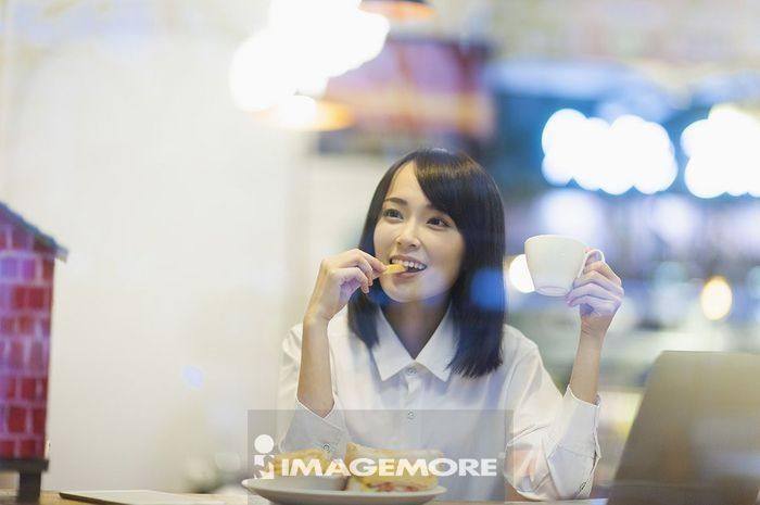 一位办公女性在吃下午茶