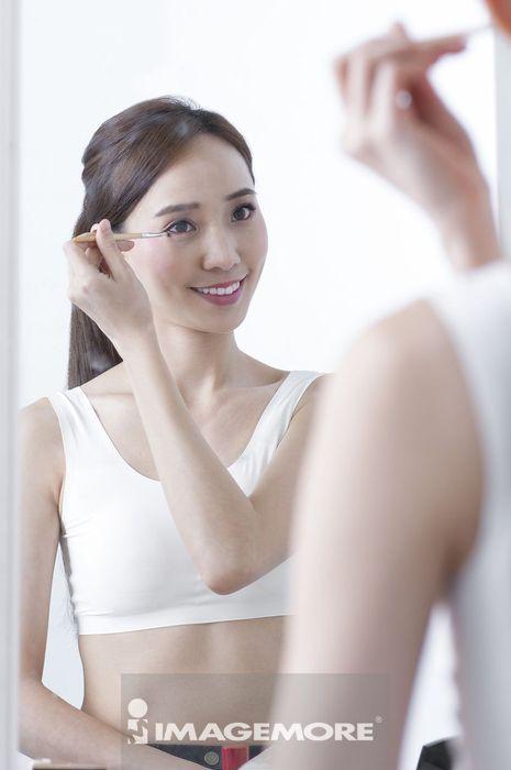 年轻女人在照镜子化眼妆