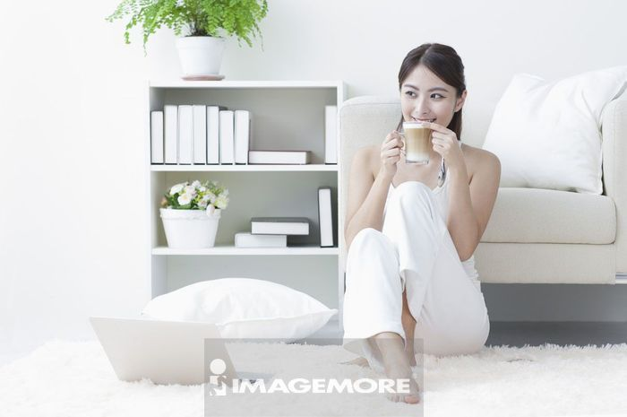 年轻女人坐在客厅喝咖啡