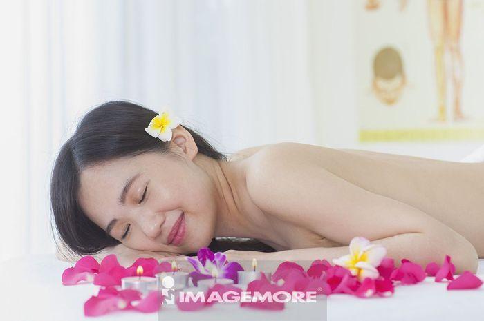 年轻女人躺在玫瑰花瓣中
