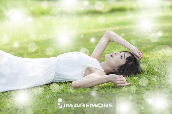 年轻女人躺在草地上