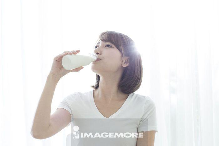 年轻女人早晨起床喝牛奶