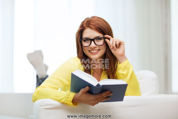 leasure and home concept - smiling teenage girl in eyeglasses reading book and sitting on couch at home