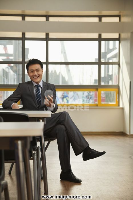 Businessman checking cell phone in company cafeteria