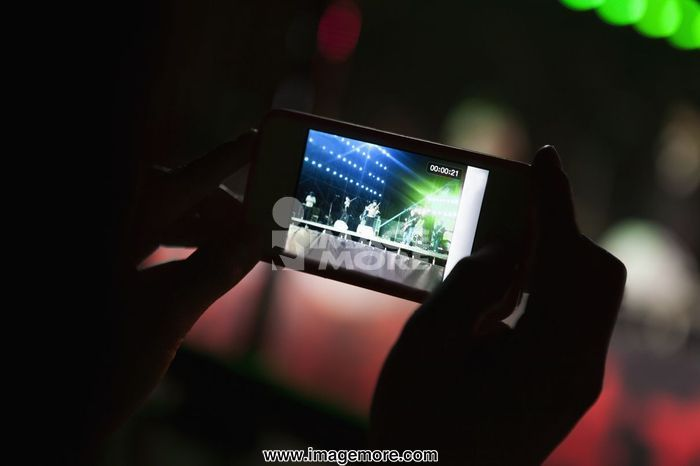 Young woman taking a photography with her smart phone at an indoor concert, Close-up on hands