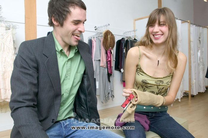 Caucasian Girl Sitting In A Trendy Boutique With Her Boyfriend And Laughing At A Pair Of Gloves