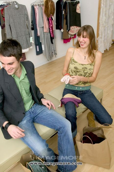 Fashionable Caucasian Couple Sitting In A Boutique And Laughing